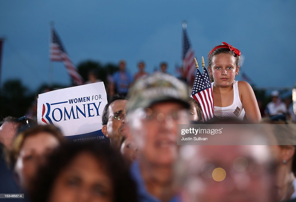 A young girl looks on as Republican presidential candidate, former Massachusetts Gov. Mitt Romney speaks during a victory rally at Pier Park on October 5, 2012 in St Petersburg, Florida. Mitt Romney is campaigning in Virginia coal country and in Florida.