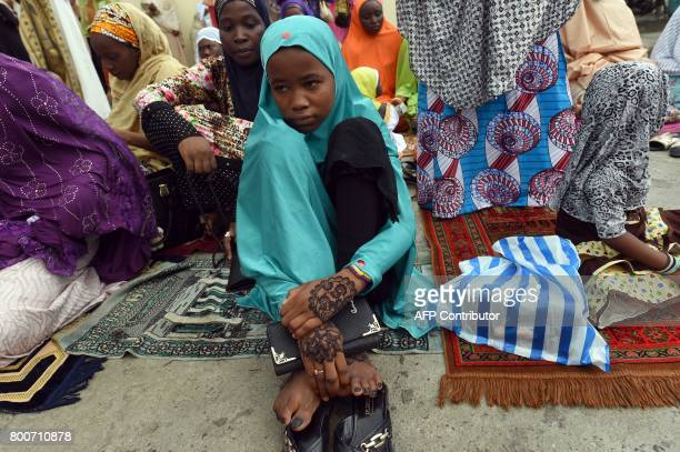 A young girl looks on as she attends the Eid alFitr prays at the Syrian Mosque at the Ikoyi district in Lagos on June 25 2017 Eid alFitr festival...