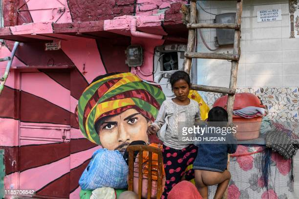 TOPSHOT A young girl looks on standing on a ladder next to a mural painted by 15 to 20 artists from 'Delhi Art Street' group to reflect nature and...