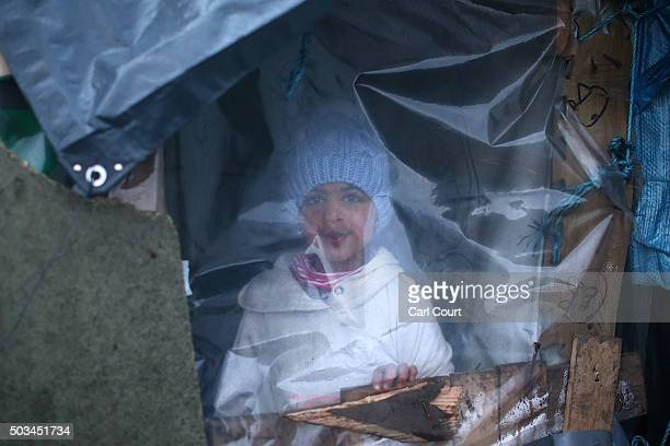 A young girl looks out from inside a shelter in the camp known as 'The Jungle' on January 5 2016 in Calais France Thousands of migrants continue to...