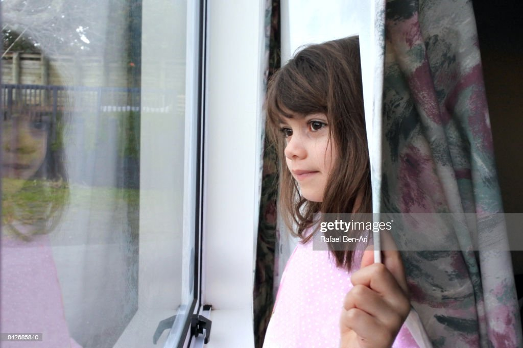 Young girl looks out of a window : Stock Photo