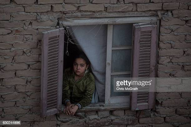 A young girl looks out of her window in an building inside the famous 'City of the Dead ' neighbourhood on December 15 2016 in Cairo Egypt The 'City...