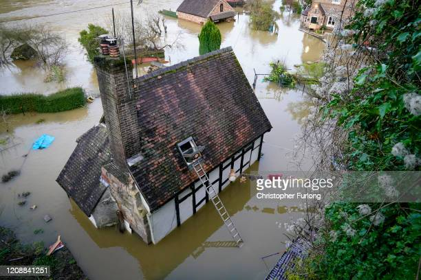 Young girl looks out the window of her marooned home in Ironbridge after the River Severn burst it's banks on February 26, 2020 in Ironbridge,...