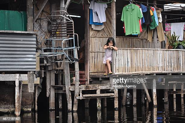 A young girl looks outside their makeshift house inside the submerged residential compund at Artex in Malabon City North of Manila on Sunday Today...