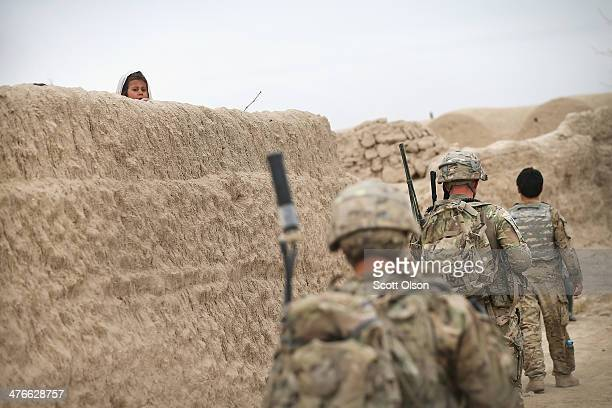 Young girl looks over the top of a wall as soldiers from the U.S. Army's 4th squadron 2d Cavalry Regimentsit participate in a joint patrol through...