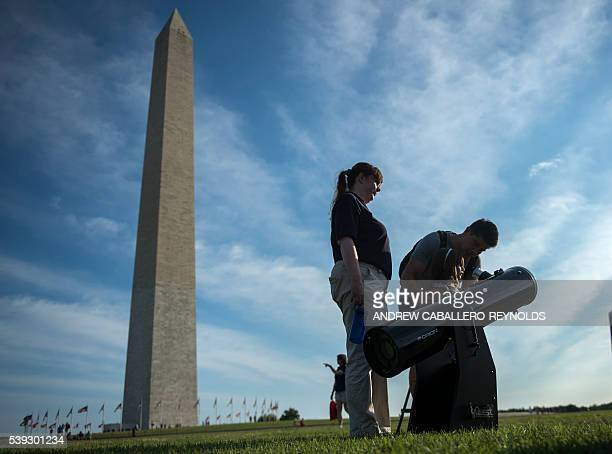 A young girl looks through a telescope at the sun near the Washington monument during an astronomy festival in Washington DC on June 10 2016 / AFP /...
