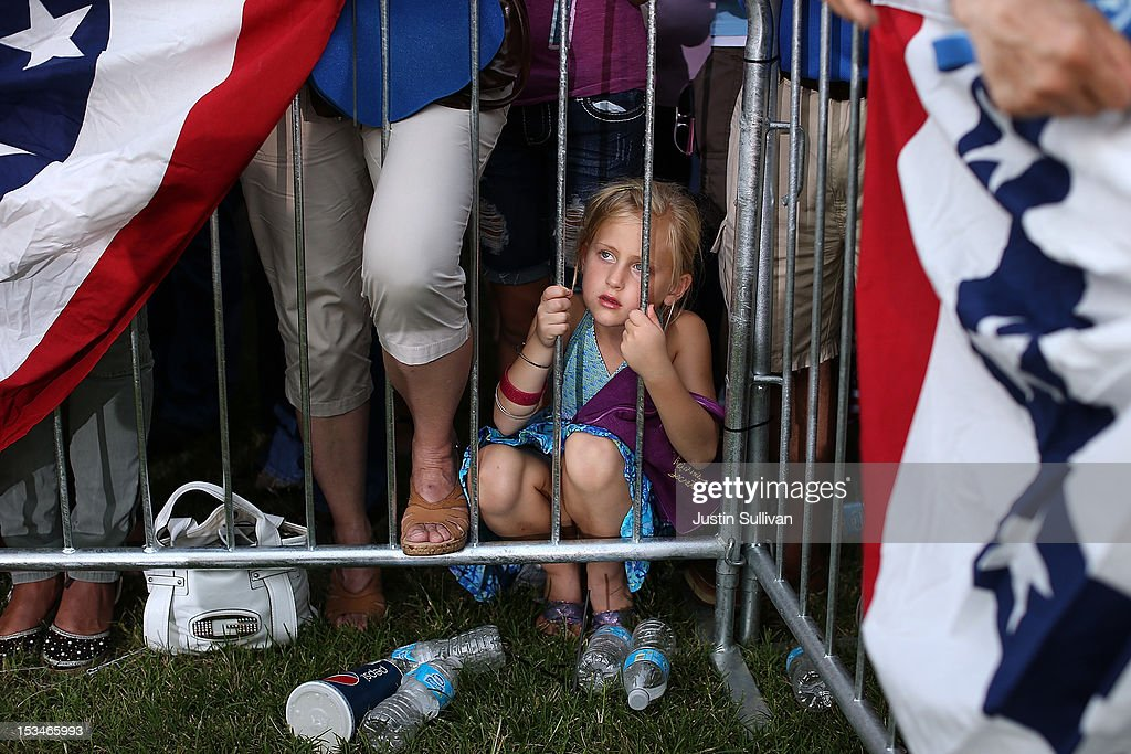 A young girl looks through security fencing as Republican presidential candidate, former Massachusetts Gov. Mitt Romney speaks during a victory rally at Pier Park on October 5, 2012 in St Petersburg, Florida. Mitt Romney is campaigning in Virginia coal country and in Florida.