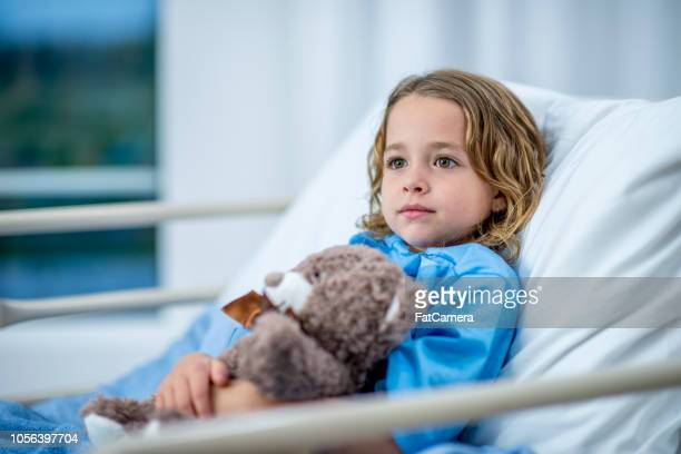 young girl lying in a hospital bed looking stoic - cancer illness stock pictures, royalty-free photos & images