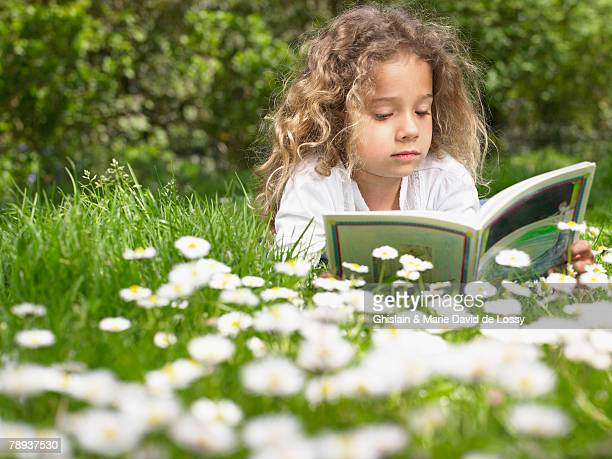 Young girl lying in the grass reading.