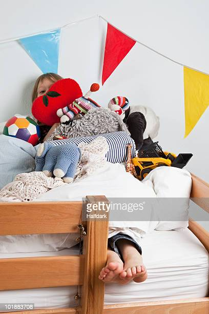 A young girl lying on a bunk bed covered in stuffed toys