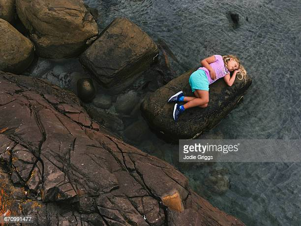 Young girl lying on a rock down by the water