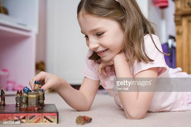 Young girl lying on bedroom floor playing with chess set