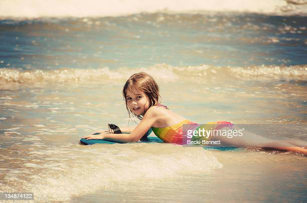 young girl lying on boogy board on shore - little girl laying on the beach stock photos and pictures