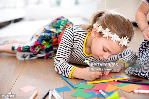 Young girl lying on floor and drawing