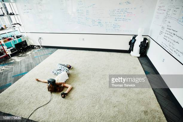 Young girl lying on floor of computer lab while using virtual reality headset