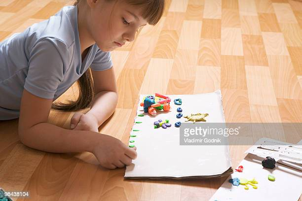 young girl lying on floor playing with modelling clay