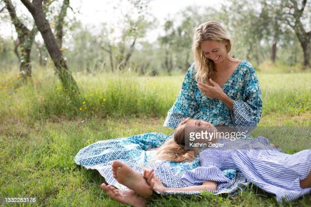young girl lying on her mother's lap - italia stock pictures, royalty-free photos & images