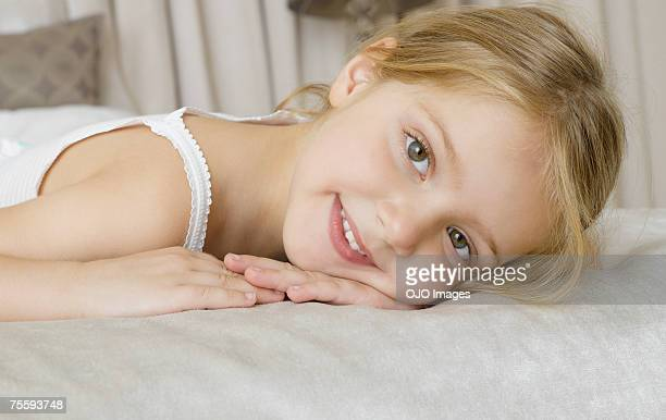 A young girl lying on her stomach on a bed