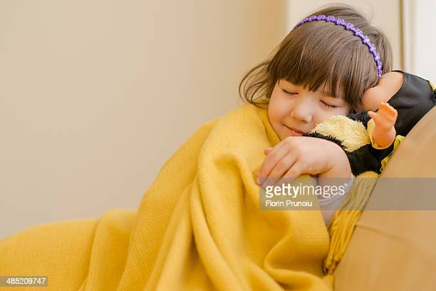 Young girl lying on sofa pretending to sleep