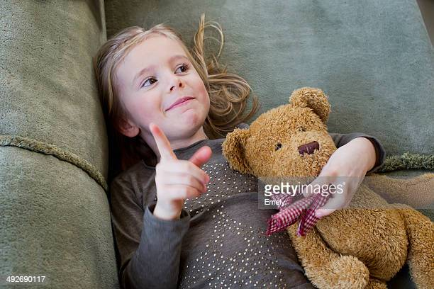 Young girl lying on sofa with her teddy bear