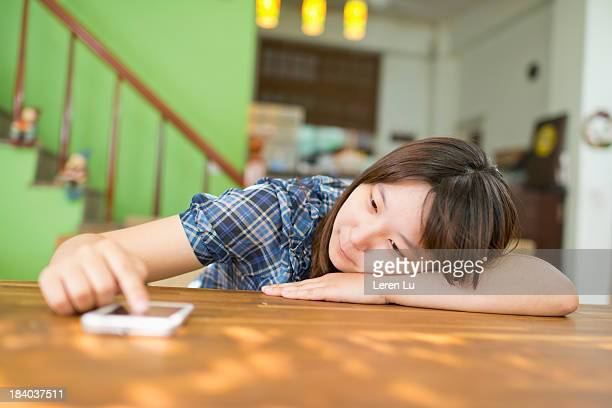 Young girl lying on table and touching smartphone