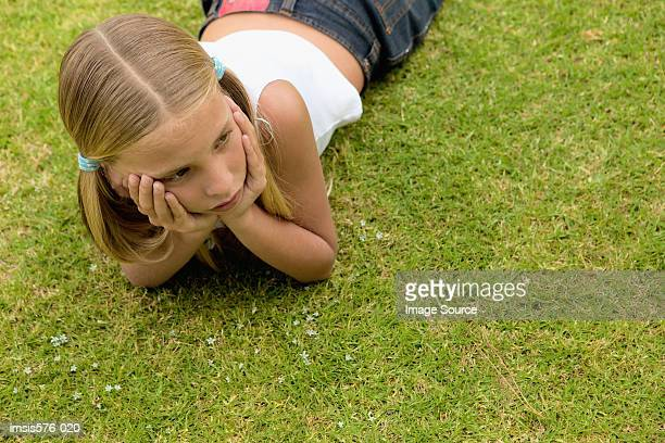 young girl lying on the grass - lying on front stock pictures, royalty-free photos & images