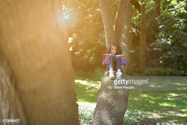 Young girl lying on tree branch looking at book
