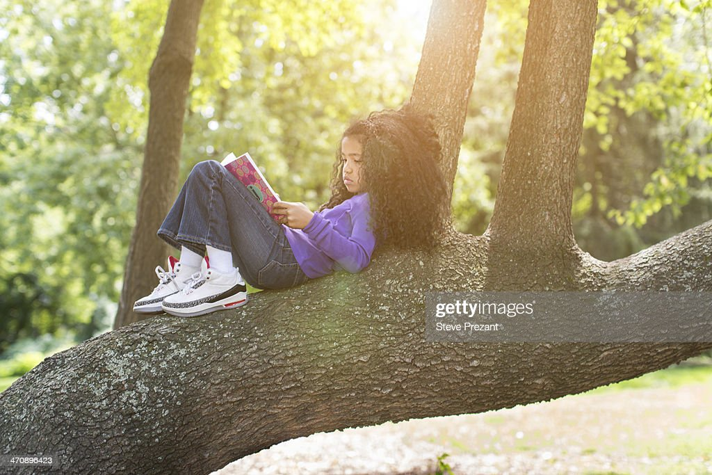 Young girl lying on tree branch reading book : Stock Photo