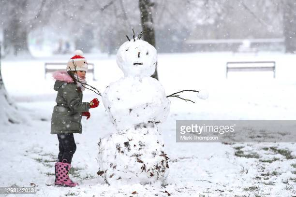 Young girl makes a snowman on January 24, 2021 in Northampton, England. Parts of the country saw snow and icy conditions as arctic air caused...