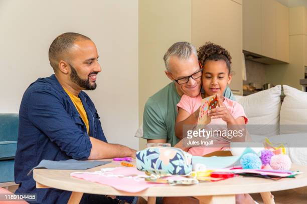 young girl makes a valentines card with her two fathers - lgbtq  and female domestic life fotografías e imágenes de stock