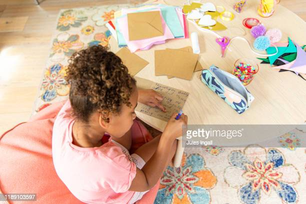 young girl making a card - thisisaustralia stock pictures, royalty-free photos & images
