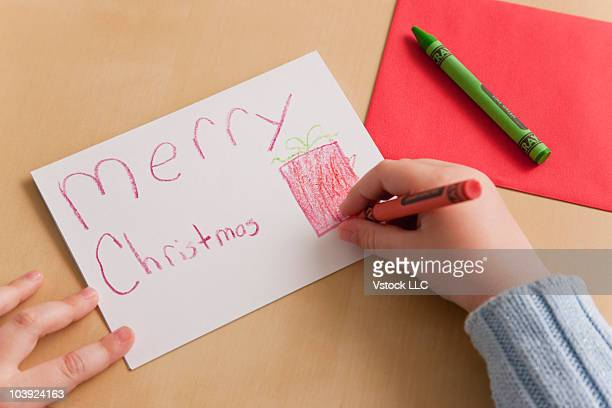 Young girl making a Christmas card