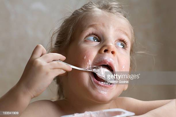A young girl making a mess out of eating yogurt
