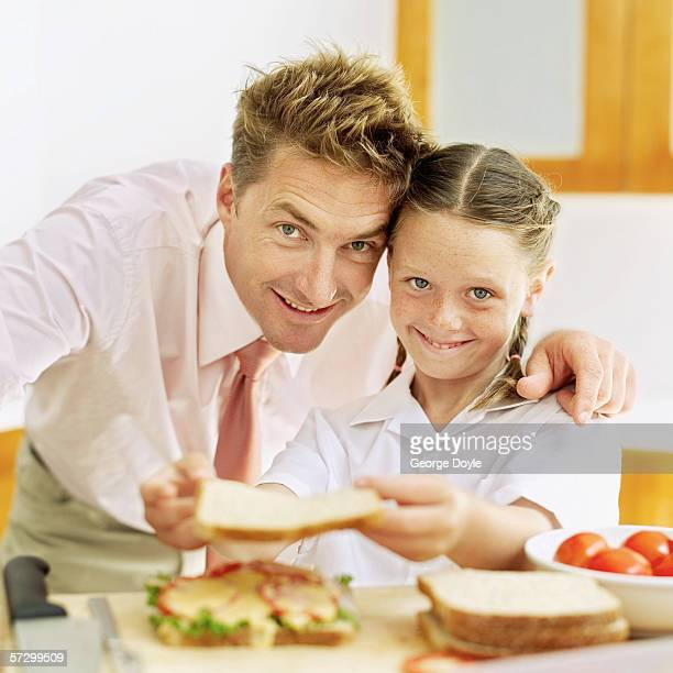 Young girl (8-10) making a sandwich with a young man standing by watching
