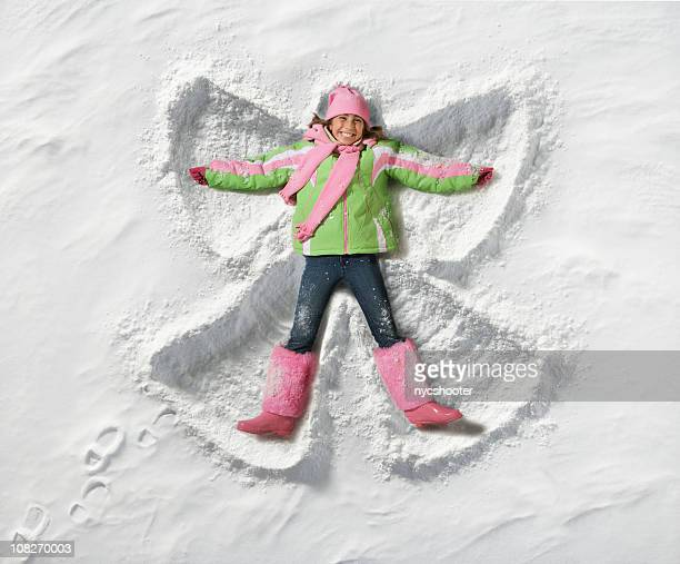 young girl making a snow angel - snow angel stock photos and pictures