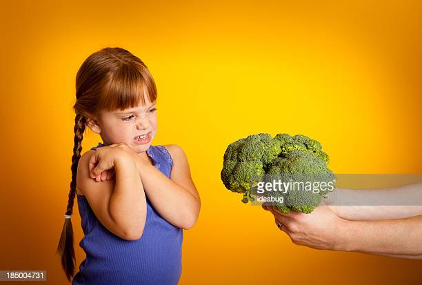 Young Girl Making  Face At Broccoli Being Held Towards Her