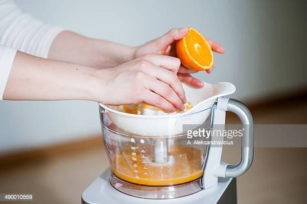 Young girl making fresh orange juice