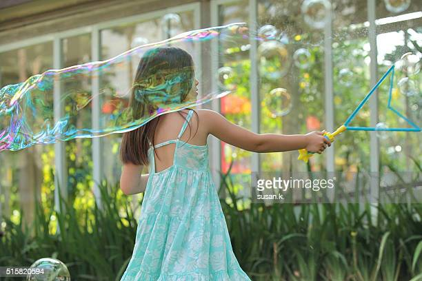 Young girl making giant soap bubbles at the garden