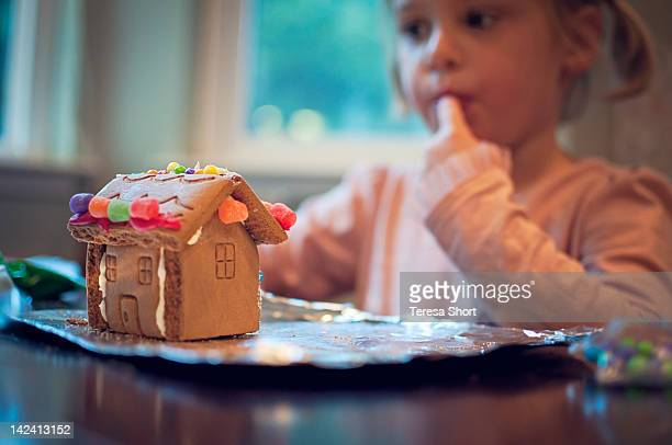 Young girl making gingerbread house