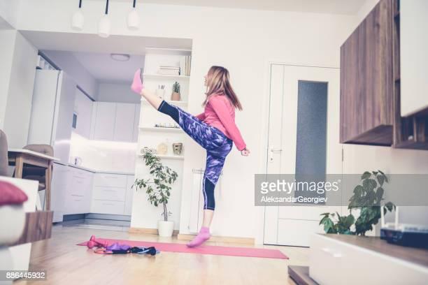 リビング ルームでキック ボックス フィットネス運動を作る少女