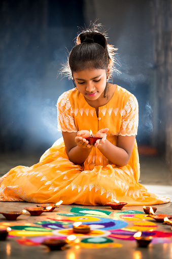 Young Girl making Rangoli, decorating with oil lamps for Diwali 615993442