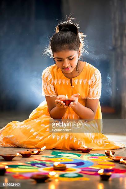 young girl making rangoli, decorating with oil lamps for diwali - diwali celebration stock photos and pictures