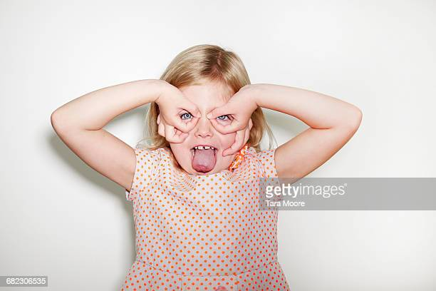 young girl making silly face - little girl sticking out tongue stock photos and pictures