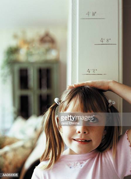 Young girl (6-8) measuring height on wall, high section