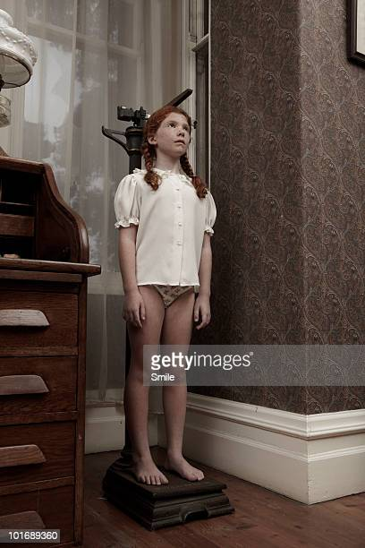 young girl measuring her height - pants stock photos and pictures
