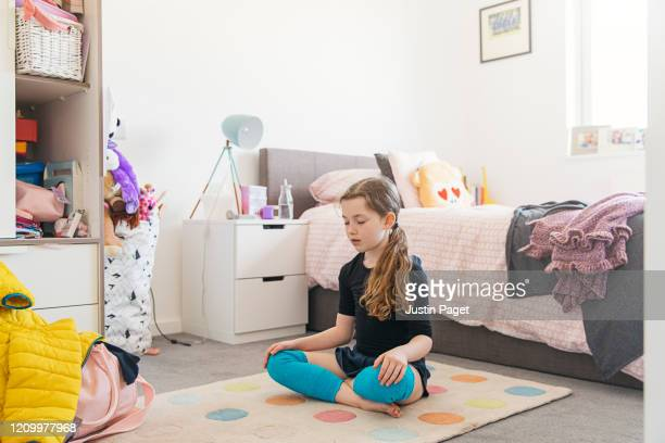 young girl meditating in her bedroom - mindfulness stock pictures, royalty-free photos & images