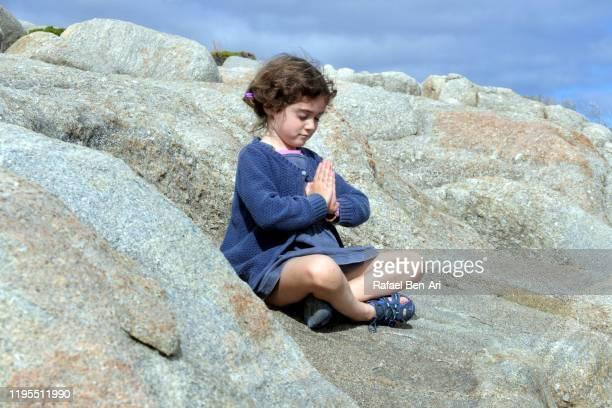 young girl meditating outdoors - rafael ben ari stock-fotos und bilder