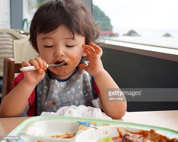 Young girl messily eats hamburger