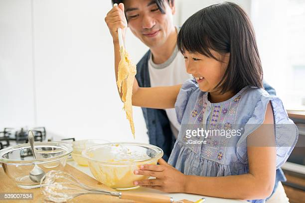 Young girl mixing cake ingredients whilst dad watches her