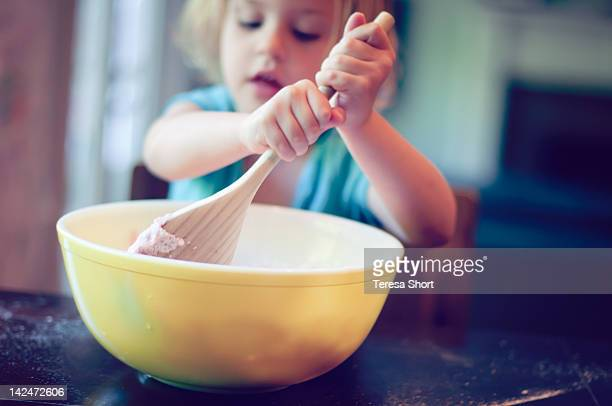 Young girl mixing food in bowl